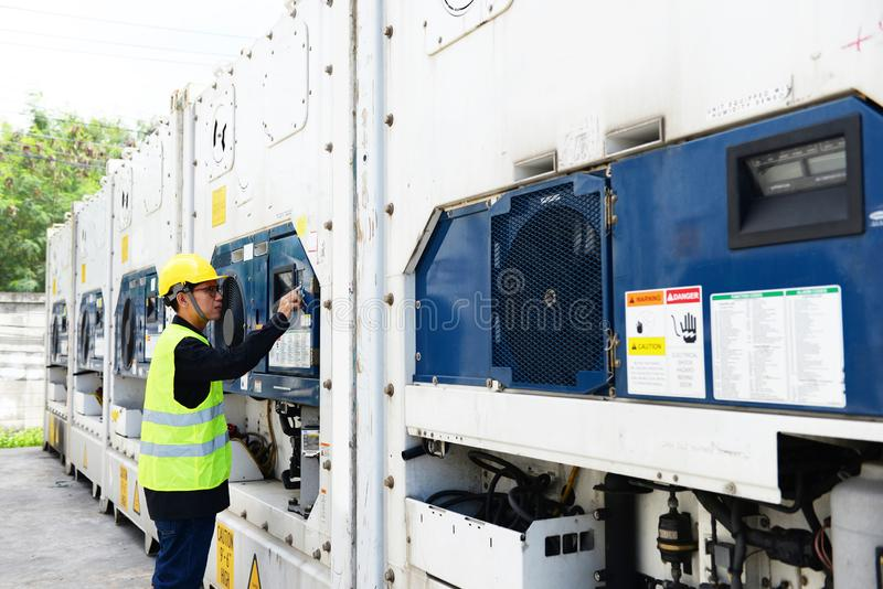 Asian man reefer technician is seriously working and monitoring reefer container. At the port stock photo
