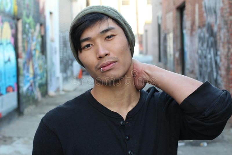 Asian man rocking a beanie outdoors.  stock photography