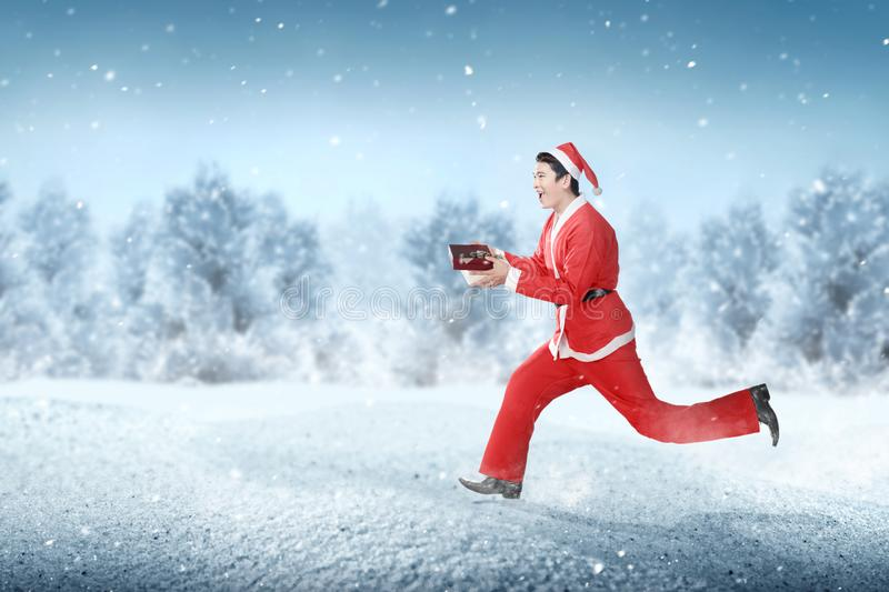 Asian man in Santa costume running while holding the gift box royalty free stock image