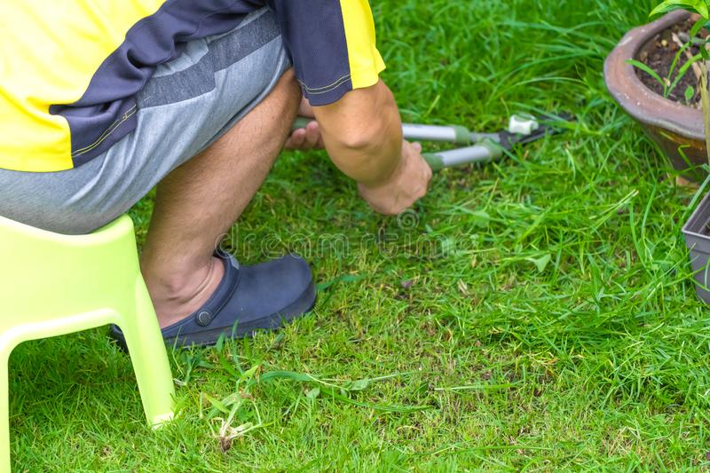 Asian man sat on plastic chair and cut the grass in his garden in the front of home. Asian man sat on plastic  chair and cut the grass in his garden in the front royalty free stock image