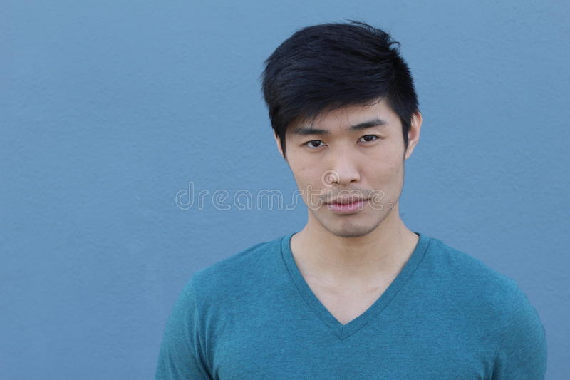 Asian man with serious expression over blue background with copy space stock image