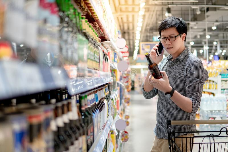 Asian man shopping beer using phone. Asian man using phone shopping beer in supermarket. Male shopper with shooping cart choosing beer bottle in grocery store stock photo