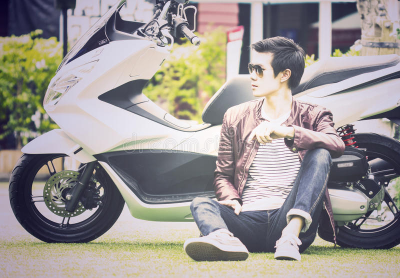 Asian man sitting on ground with his scooter outdoor stock image