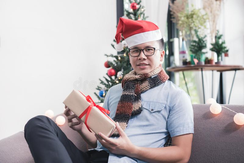 Asian man sitting on sofa holding gift box,christmas day concept royalty free stock image