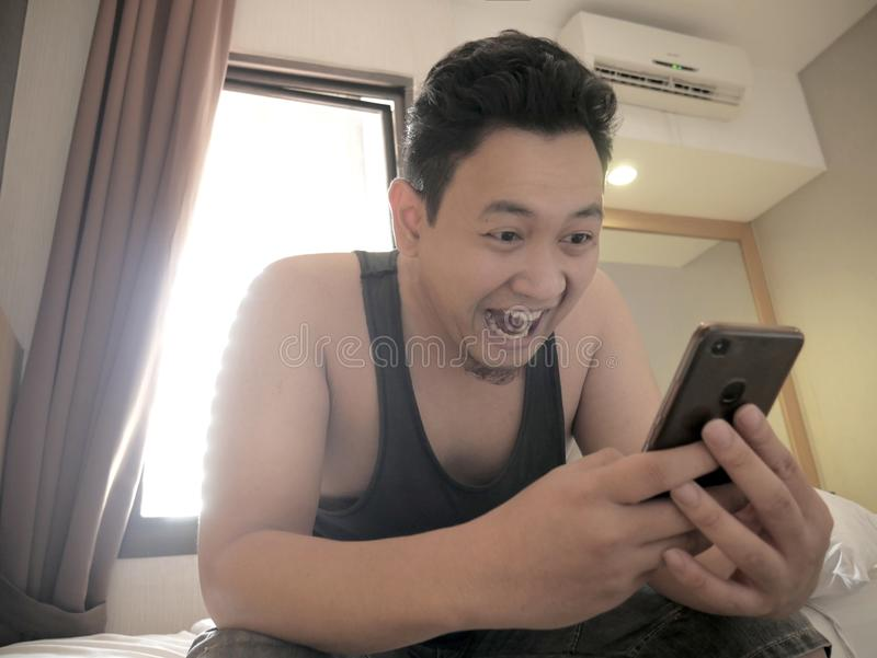 Asian man having good news on phone when waking Up on bed in the morning stock photography