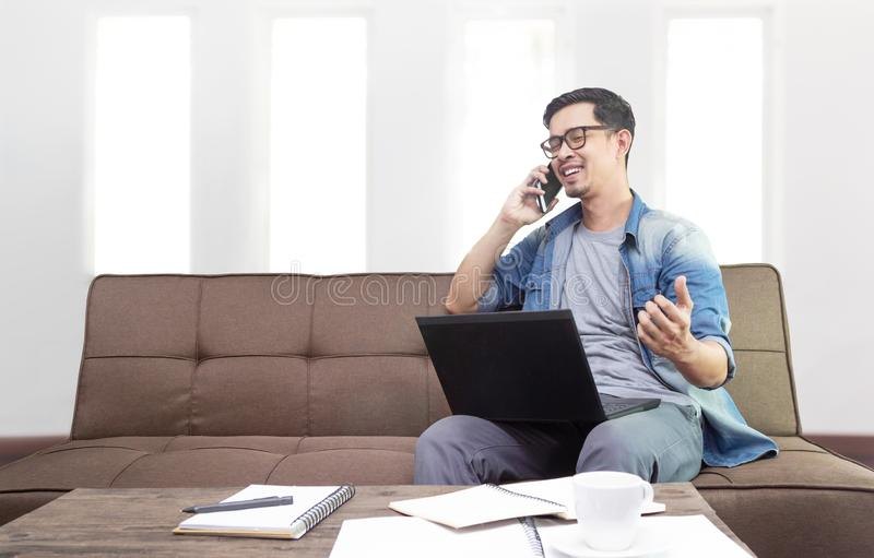 Asian man smiling and using smartphone royalty free stock photography