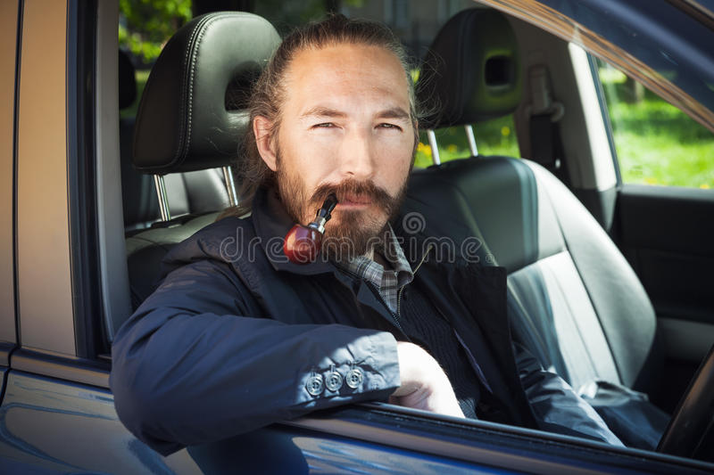 Asian man smoking pipe. Driver of modern car. Asian man smoking pipe. Driver of modern Japanese crossover suv car, portrait in open car window stock photography