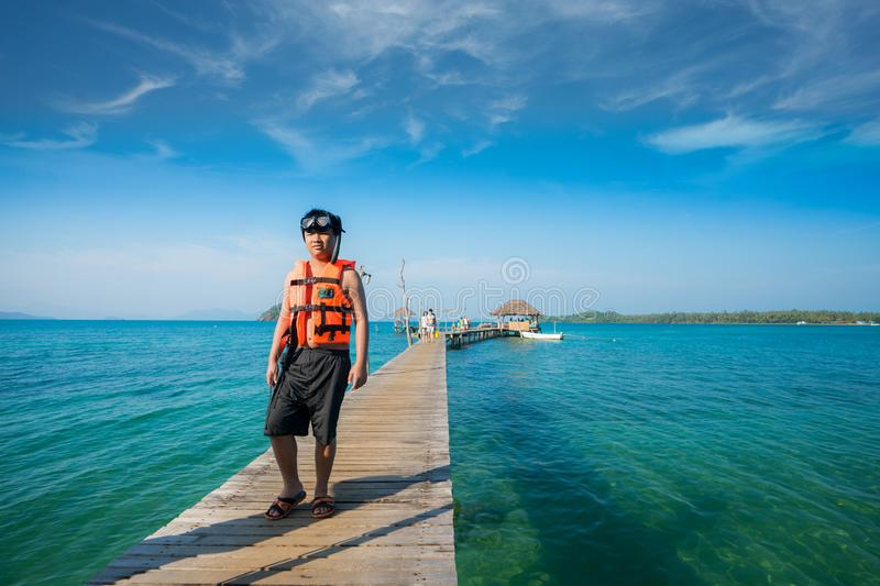 Asian man with snorkeling mask walking on the wooded bridge royalty free stock photo