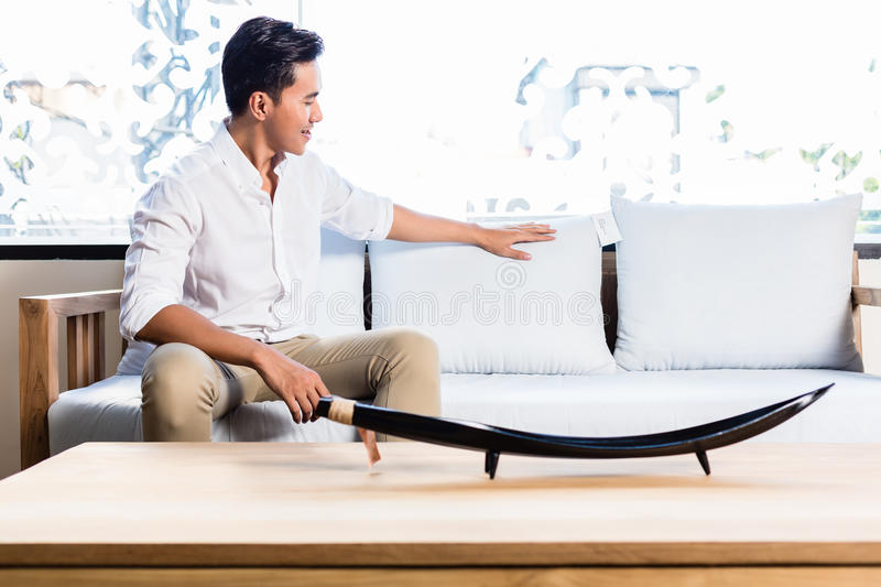 Asian man on sofa couch in furniture store. Asian Indonesian man sitting on sofa couch in furniture store showroom stock photo