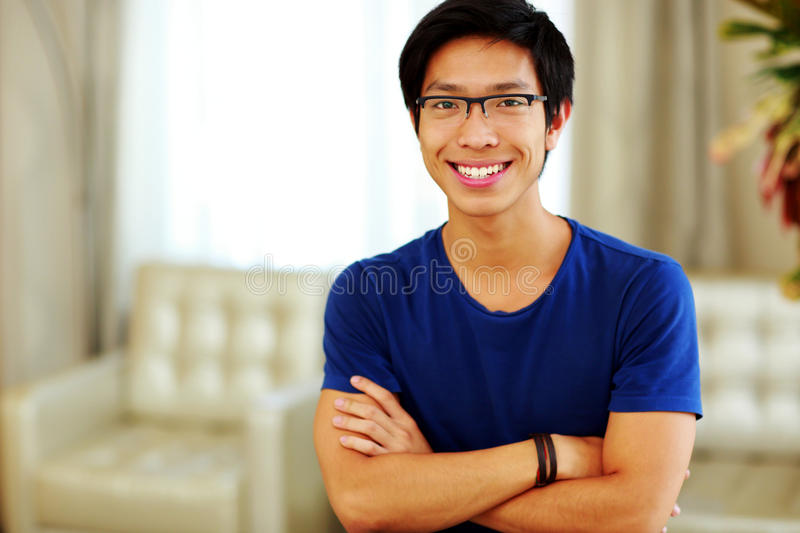 Asian man standing with arms folded. Happy asian man standing with arms folded at home stock photos