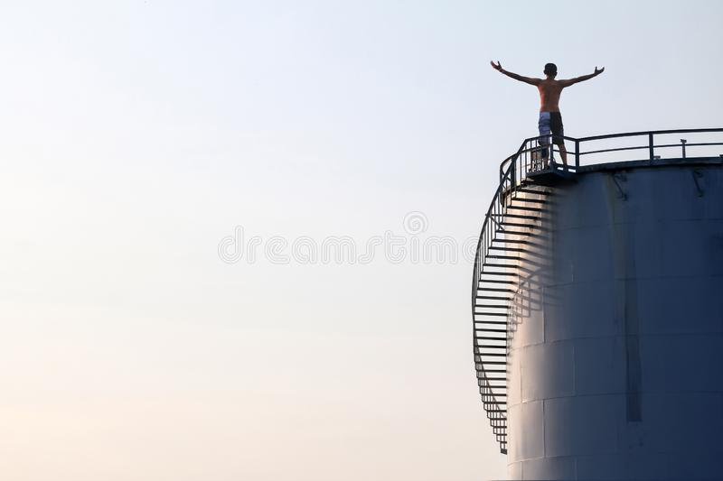 Asian man standing on the top of a large white Industrial tanks for petrol and oil stock photos