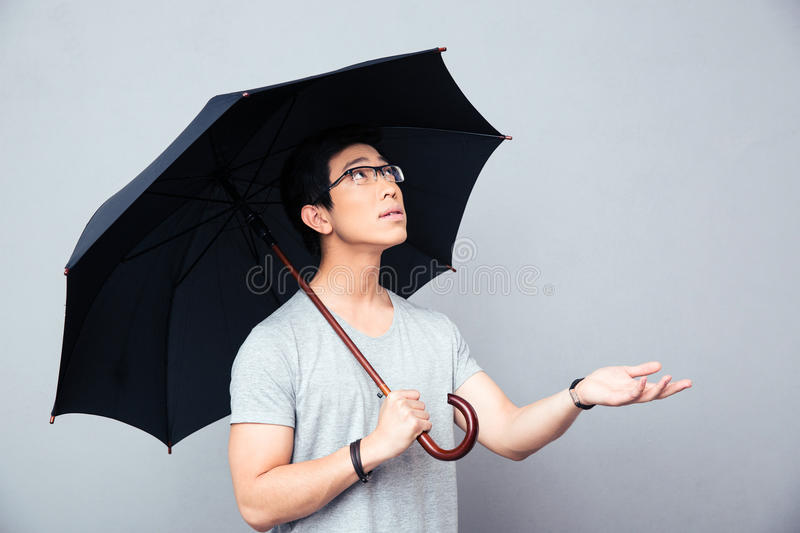 Asian man standing with umbrella stock image