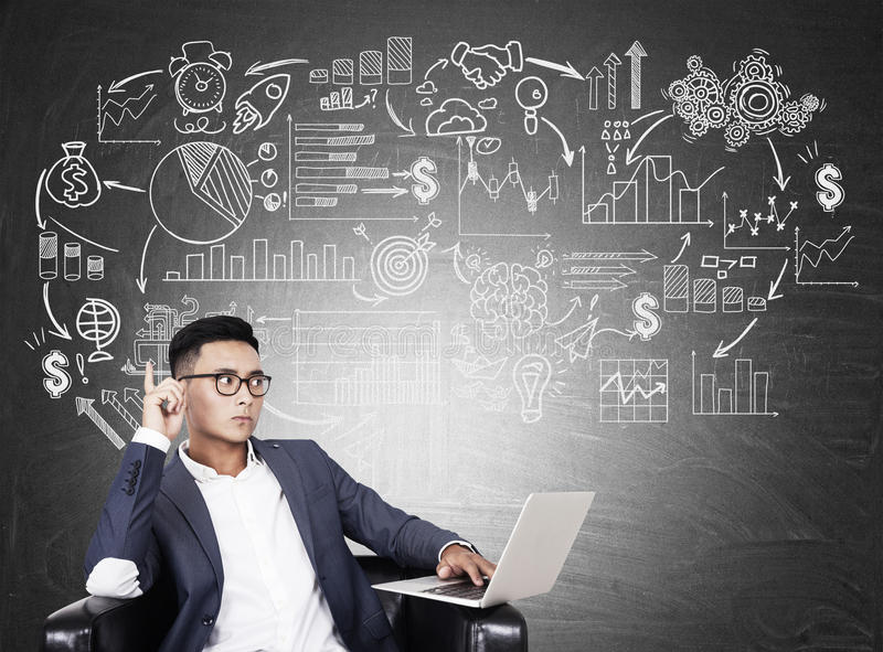Asian man and startup sketch. Asian man in glasses sitting in leather armchair with white laptop near startup sketch. Concept of development stock photography