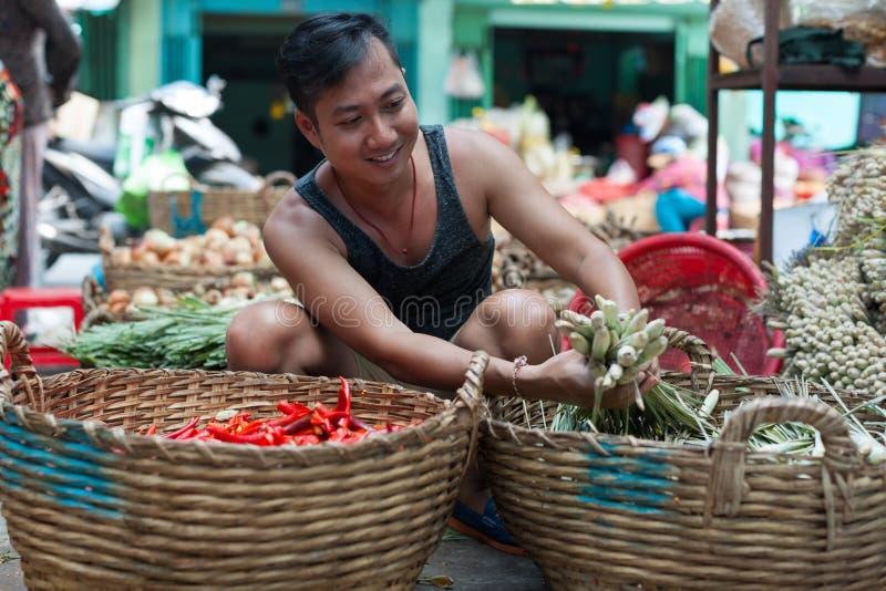 Asian man street market seller bunch green onion. Asian man on street market seller hold bunch of green onion stock image