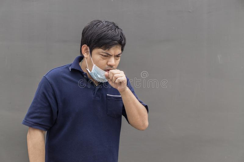 Asian man in the street wearing protective masks., Sick man with flu wearing mask and blowing nose into napkin as epidemic flu con royalty free stock image