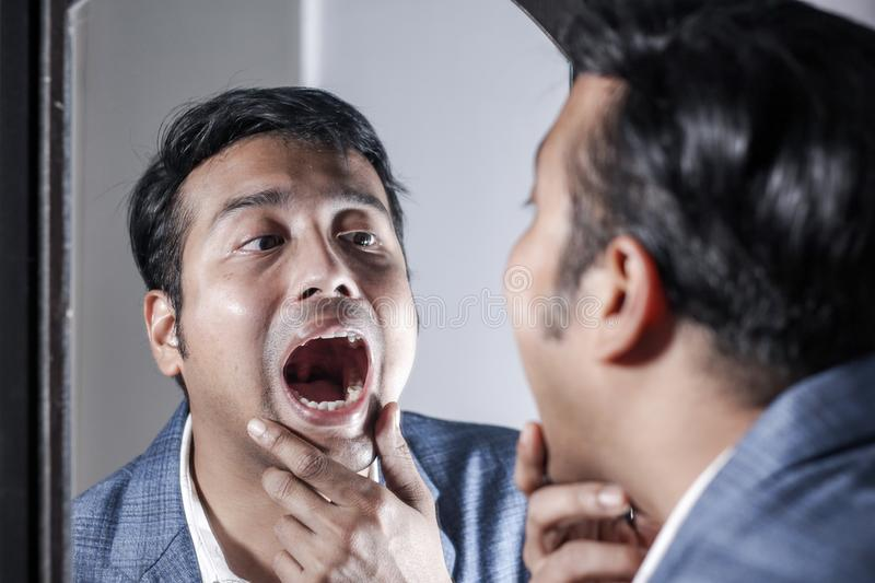 Asian man in suit looking after his appearance in front of a mirror beauty styling lifestyle. Asian man in suit looking after his appearance in front of a royalty free stock image