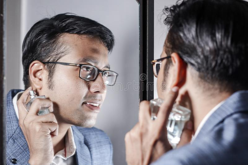 Asian man in suit looking after his appearance in front of a mirror beauty styling lifestyle. Asian man in suit looking after his appearance in front of a stock photo