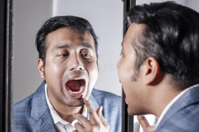 Asian man in suit looking after his appearance in front of a mirror beauty styling lifestyle. Asian man in suit looking after his appearance in front of a stock image