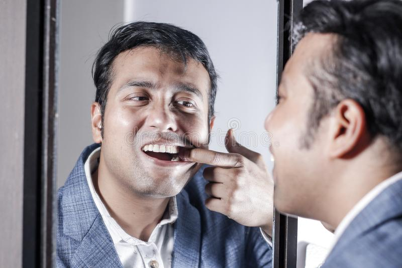 Asian man in suit looking after his appearance in front of a mirror beauty styling lifestyle. Asian man in suit looking after his appearance in front of a royalty free stock images