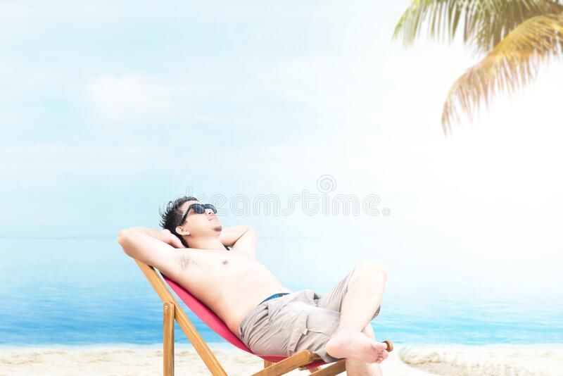 Asian man with sunglasses relaxing on the beach chair stock photos