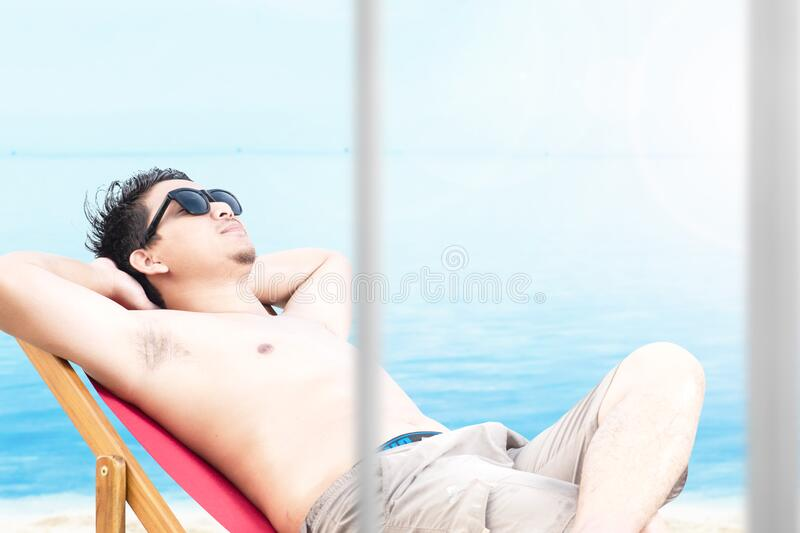 Asian man with sunglasses relaxing on the beach chair royalty free stock photography