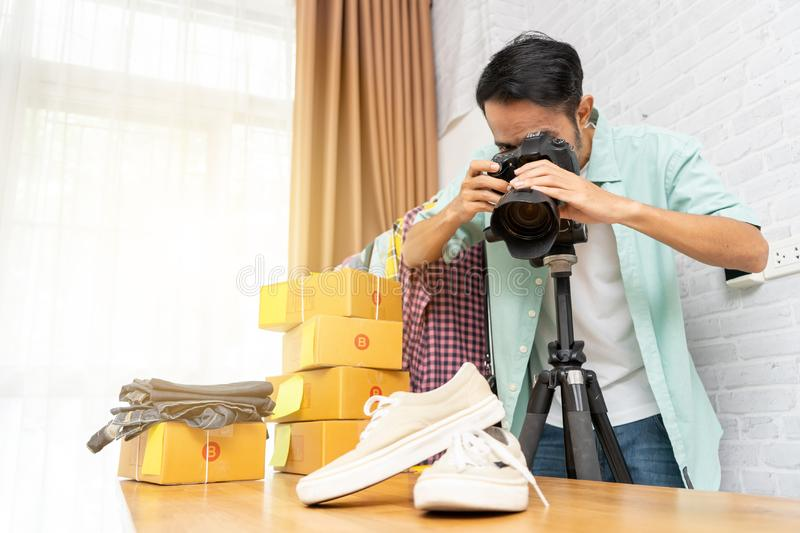Asian man taking photo to shoes with digital camera for post to selling online on the internet royalty free stock photos