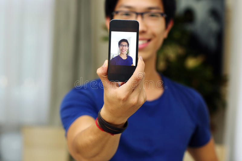 Asian man taking self picture with smartphone. Smiling asian man taking self picture with smartphone camera. Focus on smartphone stock images
