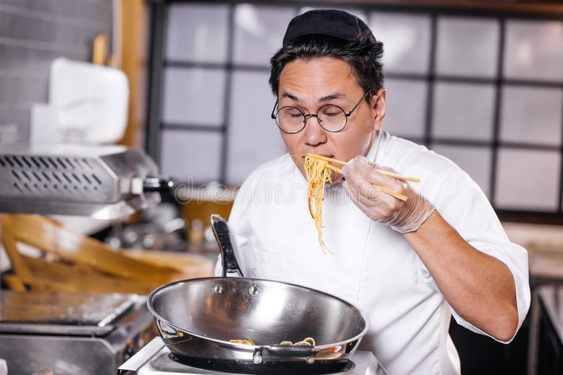 Asian man tasting prepared noodles in the kitchen royalty free stock images
