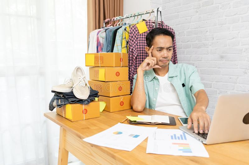 Asian man think hard serious working laptop computer at home selling online royalty free stock image