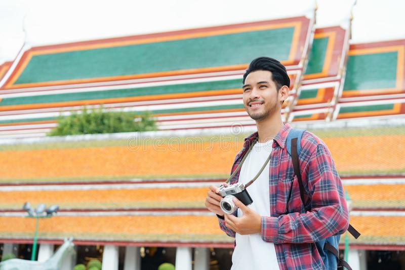 Asian man tourist walk taking photo with film camera  at Wat Suthat Thepwararam Ratchaworawihan Bangkok, Thailand in the summer ti royalty free stock photos