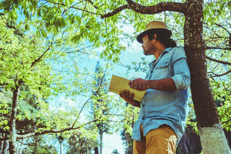 Asian man travel nature. Travel relax. Reading book On the in the park. in summer. Education stock photos