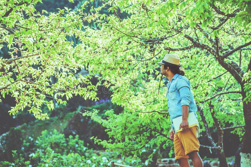 Asian man travel nature. Travel relax. Reading book On the in the park. in summer. Education stock photography