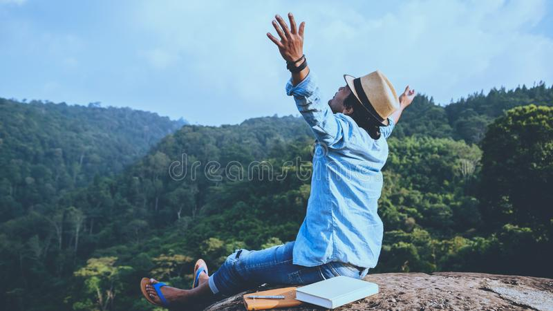 Asian man travel relax in the holiday. seats relax read books on rocky cliffs. On the Moutain summer. In Thailand. Asian man travel relax in the holiday. seats royalty free stock image