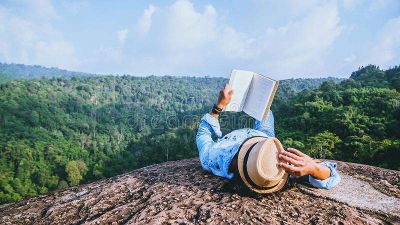 Asian man travel relax in the holiday. sleep relax read books on rocky cliffs. On the moutain summer. Education stock images
