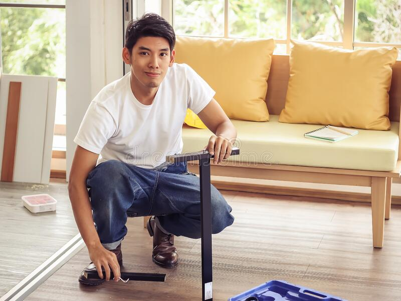 Asian man trying to assemble knockdown furniture and getting confused. Young and handsome Asian man trying to assemble knockdown furniture and getting confused royalty free stock images