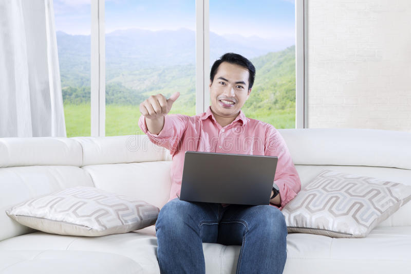 Asian man uses laptop in living room. Handsome Asian man using a laptop computer while showing OK gesture and sitting on the couch at home stock photos