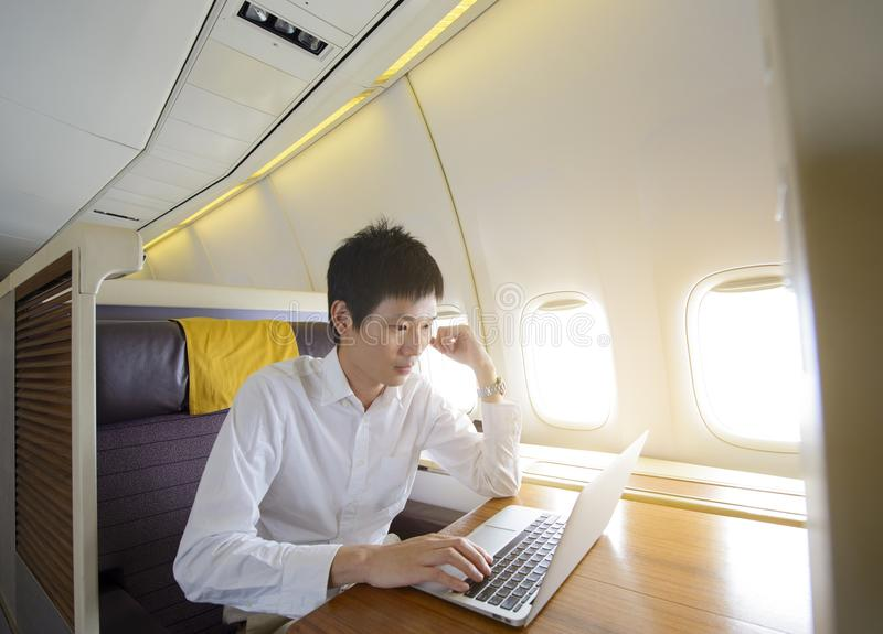 Asian man using laptop on first class airplane.  stock image