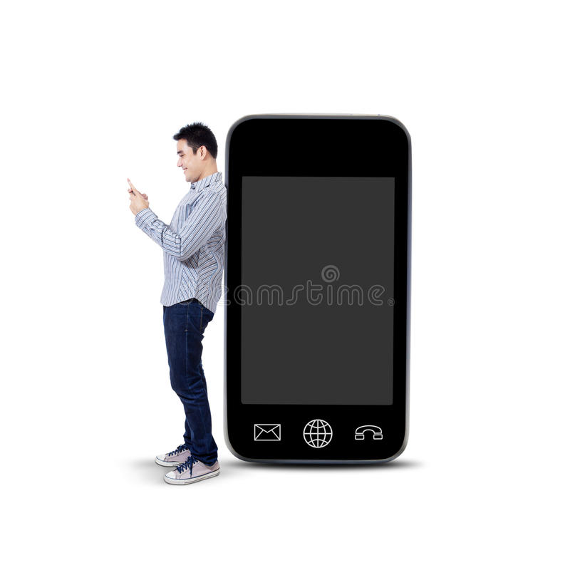Asian man using mobile phone and standing next to big smartphone. Asian man using a mobile phone and standing next to big smartphone isolated on white background stock photo