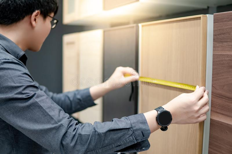 Asian man using tape measure on cabinet materials royalty free stock photography