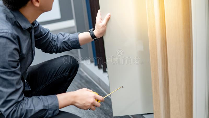 Asian man using tape measure on cabinet materials royalty free stock photos