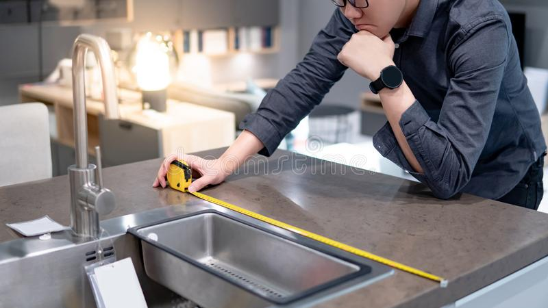 Asian man using tape measure on kitchen counter royalty free stock image