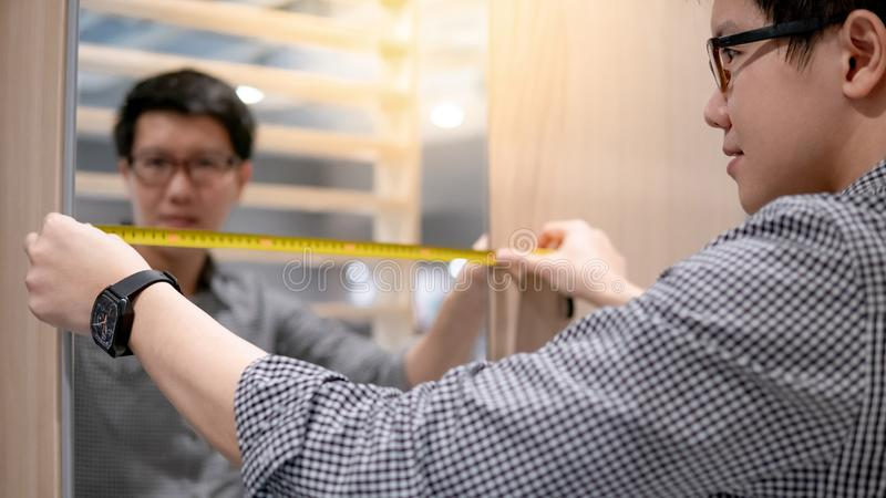 Asian man using tape measure on modern closet. Young Asian man using tape measure for measuring mirror on modern wooden cabinet in walk-in closet showroom stock photography