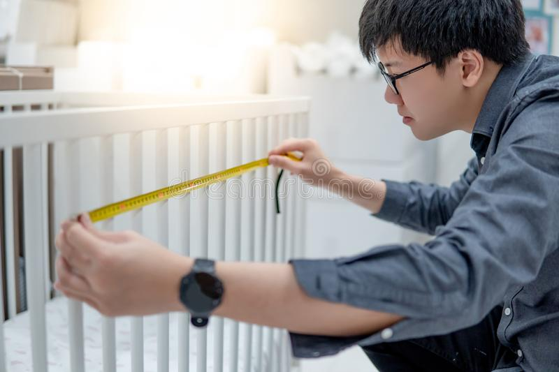 Asian man using tape measure on toddler bed rails. Asian man using tape measure for measuring dimension of toddler bed rails length and gap. Choosing furniture royalty free stock photography