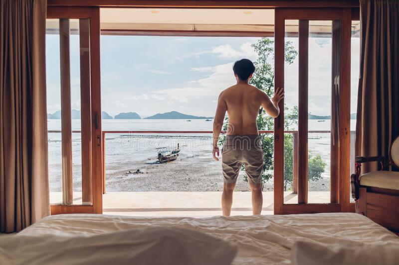 Man wake up in the room with sea view in the morning. Concept of vacation. royalty free stock image