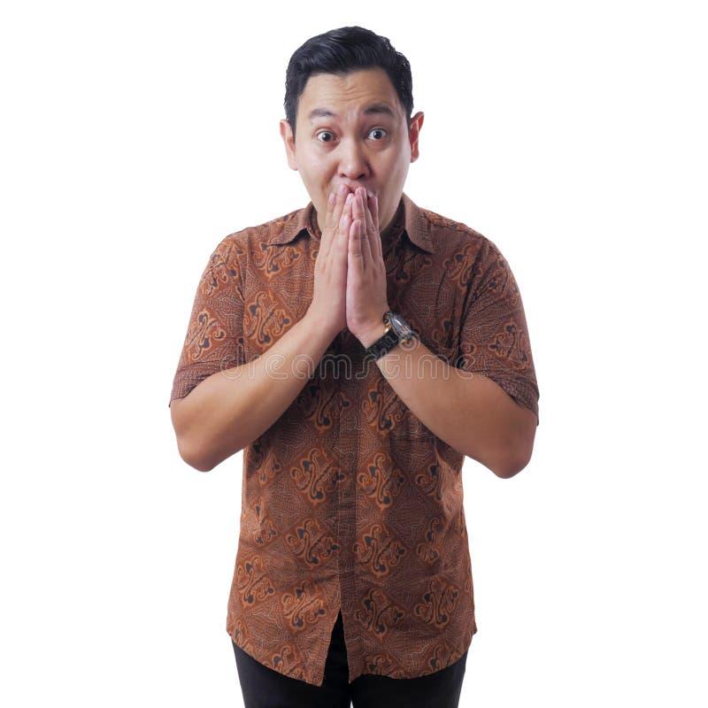 Asian Man Wearing Batik Shirt Shocked and Closing his Mouth royalty free stock photo