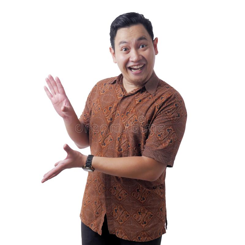 Asian Man Wearing Batik Shirt Shocked to See Something on his Side royalty free stock image
