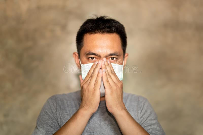 Asian man wearing a face mask with hand cover his mouth while coughing. Asian man wearing a face mask with hand cover his mouth while coughing stock photos