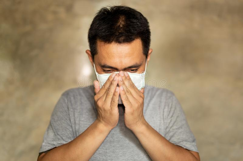 Asian man wearing a face mask with hand cover his mouth while coughing. Asian man wearing a face mask with hand cover his mouth while coughing royalty free stock images