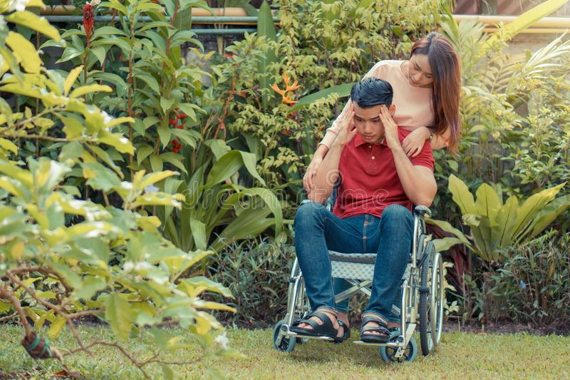 Asian Man in a wheelchair and Unhappy and painful. A woman standing behind the wheelchair and is encouraging her husband, whose fe royalty free stock photos