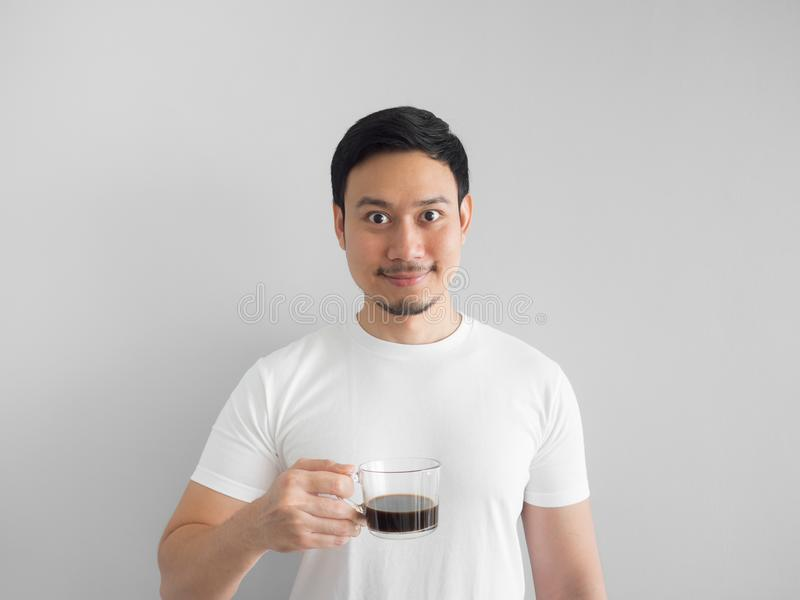 Man in white t-shirt drinks a cup of coffee. stock image